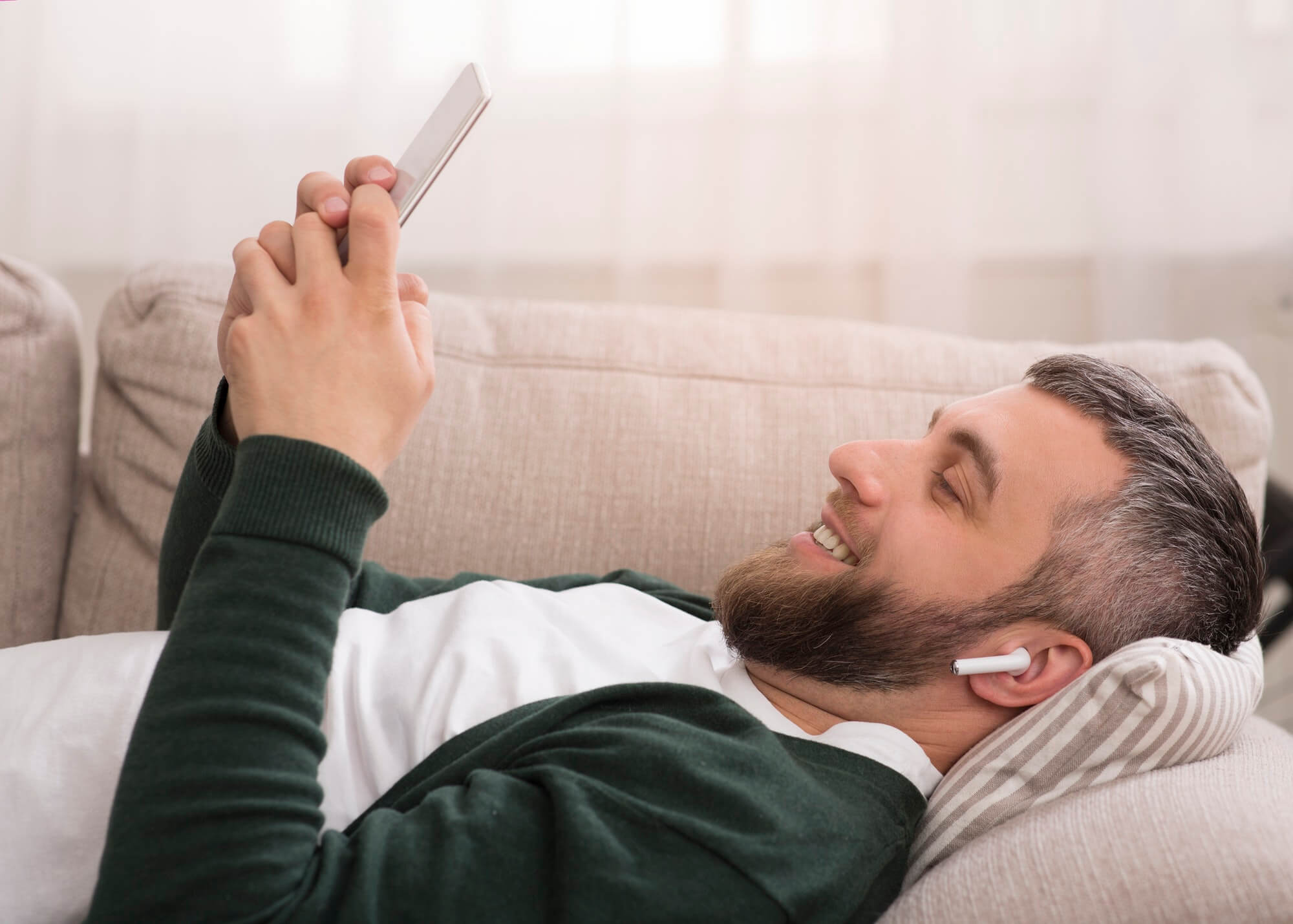 Cheerful man watching movies on digital tablet with wireless earphones